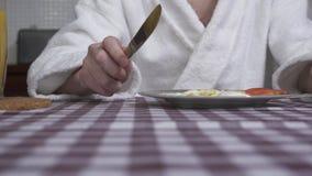Ανθρώπινο τέμνον αυγό χεριών που βρίσκεται στο πιάτο με το δίκρανο και το μαχαίρι κοντά επάνω Το γυαλί και το βάζο χυμού από πορτ απόθεμα βίντεο