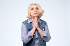 Ανώτερη γυναίκα που ικετεύει και που προσεύχεται μαζί με την έκφραση ελπίδας στο πρόσωπο στοκ εικόνες