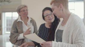 Ανώτερη γυναίκα που παρουσιάζει στους φίλους παλαιές άσπρες και μαύρες φωτογραφίες της Ομάδα επικοινωνίας τριών μέσης ηλικίας ώρι φιλμ μικρού μήκους