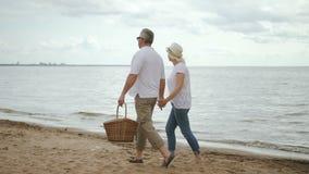 Ανώτεροι εραστές που συναντούν την ημέρα στην παραλία Περπάτημα και στην ακτή μετά από το πικ-νίκ απόθεμα βίντεο