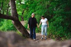 Ανώτερο ζεύγος που περπατά μαζί σε ένα δάσος, κινηματογράφηση σε πρώτο πλάνο στοκ φωτογραφία