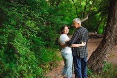 Ανώτερο ζεύγος που περπατά μαζί σε ένα δάσος, κινηματογράφηση σε πρώτο πλάνο στοκ εικόνα