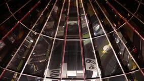 Αντανάκλαση των ανθρώπων που παίρνουν την κυλιόμενη σκάλα μέσα στη κυρία είσοδος λεωφόρων αγορών απόθεμα βίντεο