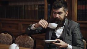 Αξιοσέβαστο τσάι κατανάλωσης ατόμων στο υπόβαθρο της βιβλιοθήκης Το ντεμοντέ άτομο κρατά το φλυτζάνι με το τσάι Άτομο στο κλασικό φιλμ μικρού μήκους