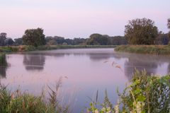 Αργός ρέοντας ποταμός Warta στην ομίχλη πρωινού στοκ εικόνα