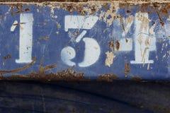 Αριθμός εκατό τριάντα που χρωματίζονται στο σκουριασμένο μπλε μέταλλο στοκ φωτογραφία με δικαίωμα ελεύθερης χρήσης