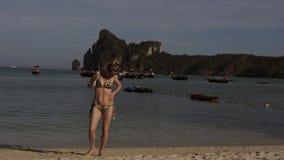 Αρκετά νέα μαυρισμένη ξανθή γυναίκα στο μπικίνι στην παραλία άμμου Buttering το σώμα της με το suntan πετρέλαιο απόθεμα βίντεο