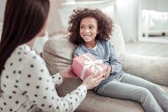 Αρκετά συμπαθητική κυρία που παρουσιάζει ένα δώρο σε ένα κορίτσι στοκ εικόνες