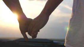Αρσενικά χέρια που κρατούν το ένα το άλλο στο υπόβαθρο ηλιοβασιλέματος Νέο ομοφυλοφιλικό ζεύγος που στέκεται σε ετοιμότητα τη στέ απόθεμα βίντεο