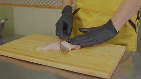Αρσενικός μάγειρας που τεμαχίζει ένα κομμάτι του στήθους κοτόπουλου φιλμ μικρού μήκους