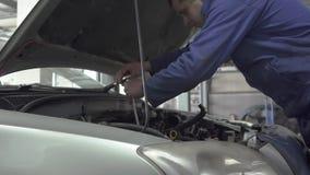 Αρσενικός νέος αυτόματος ειδικός που ξεβιδώνει το μέρος στην κουκούλα του αυτοκινήτου για την επισκευή ή την παραγωγή της επιθεώρ φιλμ μικρού μήκους