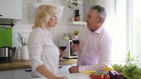 Αρσενικός συνταξιούχος που μιλά στο ανώτερο κρασί κατανάλωσης γυναικών στην κουζίνα απόθεμα βίντεο