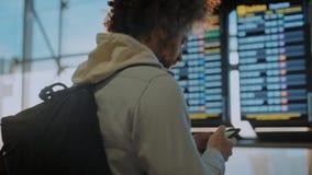 Αρσενικός χιλιετής ταξιδιώτης κοντά στην οθόνη πληροφοριών αερολιμένων απόθεμα βίντεο