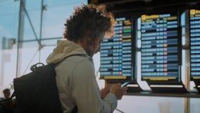 Αρσενικός χιλιετής ταξιδιώτης κοντά στην οθόνη πληροφοριών αερολιμένων φιλμ μικρού μήκους