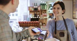 Αρσενικός πελάτης που κάνει την ανέπαφη πληρωμή για τις αγορές απόθεμα βίντεο