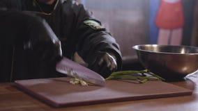 Αρχιμάγειρας που τεμαχίζει με το αιχμηρό πράσινο αρωματικό κρεμμύδι μαχαιριών στον ξύλινο πίνακα για να προετοιμάσει τη σαλάτα στ φιλμ μικρού μήκους