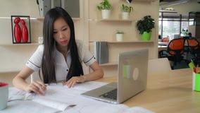 Αρχιτέκτονας γυναικών στο γραφείο που λειτουργεί με το σχέδιο στοκ φωτογραφίες