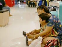 Ασιατικές μητέρα και αυτή λίγη κόρη που βάζει στα παπούτσια και που δοκιμάζει τα επάνω πρίν λαμβάνει μια απόφαση εαν πρέπει να αυ στοκ φωτογραφία με δικαίωμα ελεύθερης χρήσης
