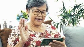 Ασιατική ανώτερη γυναίκα χρησιμοποιώντας το έξυπνο τηλέφωνο και πίνοντας ένα φλιτζάνι του καφέ στο σπίτι απόθεμα βίντεο