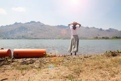 Ασιατική γυναίκα που στέκεται κοντά στον ποταμό με τη θέα βουνού στο υπόβαθρο Ευτυχείς ταξίδι και τρόπος ζωής στοκ εικόνες