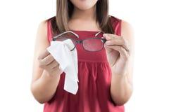 Ασιατικός γυναικών φακός γυαλιών χεριών καθαρίζοντας στοκ φωτογραφίες