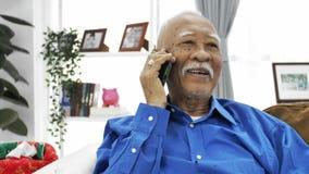 Ασιατικό ανώτερο άτομο με το άσπρο mustache που μιλά με το έξυπνο τηλέφωνο στο σπίτι, απόθεμα βίντεο