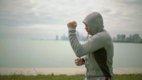 Ασκήσεις ενός νέες αθλητικές ατόμων τραίνων εγκιβωτισμού στα πλαίσια της πόλης και της λίμνης, σε αργή κίνηση r απόθεμα βίντεο