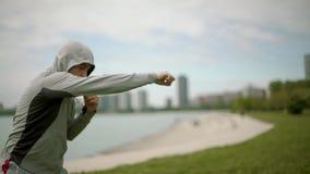 Ασκήσεις ενός οι νέες αθλητικές ατόμων τραίνων εγκιβωτισμού στα πλαίσια της πόλης και της λίμνης, περιστρέφονται τη κάμερα, σε αρ απόθεμα βίντεο