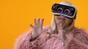 Αστεία ανώτερη γυναίκα στο κίτρινο υπόβαθρο προστατευτικών διόπτρων εικονικής πραγματικότητας, ψυχαγωγία φιλμ μικρού μήκους