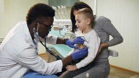 Αφρικανικός αρσενικός γιατρός που ελέγχει το ποσοστό καρδιών μικρού παιδιού που χρησιμοποιεί το στηθοσκόπιο στο γραφείο απόθεμα βίντεο