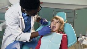 Αφρικανικός αρσενικός οδοντίατρος που μεταχειρίζεται τα δόντια του μικρού κοριτσιού απόθεμα βίντεο