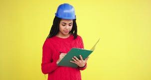 Αφρικανικός εθνικός γυναικών από μια περιοχή της κατασκευής με ένα μπλε κράνος κάνει μερικές σημειώσεις στα φύλλα της, στο στούντ απόθεμα βίντεο