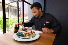 Αφρικανικό άτομο που τρώει τα σούσια σε ένα εστιατόριο στοκ φωτογραφίες με δικαίωμα ελεύθερης χρήσης