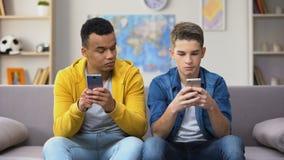 Αφροαμερικάνος και καυκάσια teens που παίζουν τα παιχνίδια στα τηλέφωνα, που παρουσιάζουν αποτελέσματα απόθεμα βίντεο