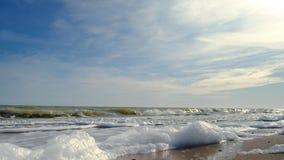 Αφρός θάλασσας, ο οποίος διαμορφώθηκε από το ράντισμα των κυμάτων σε μια κενή αμμώδη χειμερινή παραλία Κλείστε επάνω του αφρού θά απόθεμα βίντεο