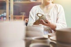 αχθοφόρος γυναικών που κάνει το κεραμικό φλυτζάνι στοκ φωτογραφία με δικαίωμα ελεύθερης χρήσης