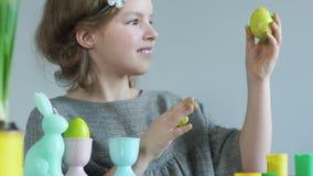 Αυγά Πάσχας χρωμάτων κοριτσιών με τα δάχτυλά της Θεραπεία τέχνης Η χαριτωμένη μαθήτρια σε ένα στεφάνι κρατά στο χέρι της έναν ανο απόθεμα βίντεο