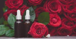 Αυξήθηκε πετρέλαιο, μπουκάλια και φρέσκα λουλούδι και φύλλα σε ένα φυσικό υπόβαθρο, βιο, οργανικό στοκ φωτογραφίες με δικαίωμα ελεύθερης χρήσης