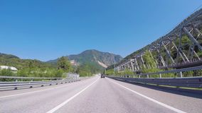 Αυτοκίνητο που κινείται σε μια εθνική οδό κοντά στους σιδηροδρόμους ενάντια στο μπλε ουρανό και τα καυκάσια βουνά σκηνή Sochi, πε απόθεμα βίντεο