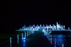 Αποβάθρα νύχτας με τους αργοσχόλους ήλιων, στα φωτεινά φω'τα, στη θάλασσα στοκ φωτογραφίες
