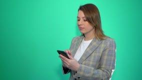 Απογοητευμένο λυπημένο ξανθό κοριτσιών στο κινητό τηλέφωνο στεμένος που απομονώνεται πέρα από το πράσινο υπόβαθρο φιλμ μικρού μήκους