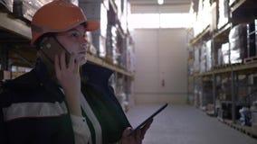 Αποθήκη εμπορευμάτων εργοστασίων, θηλυκός επιθεωρητής στο πορτοκαλί κράνος που μιλά στο κινητό τηλέφωνο και που χρησιμοποιεί τον  απόθεμα βίντεο