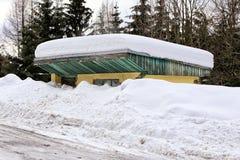 Αποκλεισμένο από τα χιόνια αχρησιμοποίητο κτήριο στάσεων λεωφορείου με βαρύ snowdrift στοκ φωτογραφία