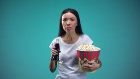 Απορροφημένος στην πλοκή της γυναίκας ταινιών που πίνει το αφρώδες νερό και που τρώει popcorn, κινηματογράφος φιλμ μικρού μήκους