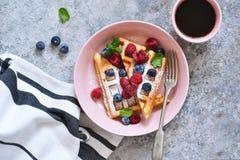Βάφλες βανίλιας με το μούρο σε ένα πιάτο για το πρόγευμα στον πίνακα κουζινών στοκ φωτογραφίες