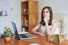 Βέβαια σύγχρονη γυναίκα στο λειτουργώντας γραφείο στην αρχή στοκ φωτογραφίες