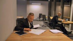 Βέβαιος κύριος επιχειρηματίας με τους συναδέλφους, ισπανικός και το αφροαμερικάνο, που εργάζονται με τα έγγραφα στο γραφείο νύχτα φιλμ μικρού μήκους