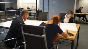 Βέβαιο businesspeople που παρουσιάζει σχεδίων για τα σχέδια στους συναδέλφους φιλμ μικρού μήκους
