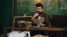 Βαθμολόγηση εκπαίδευσης και έννοια ανθρώπων Ο γενειοφόρος δάσκαλος διαβάζει ένα βιβλίο στην κατηγορία Δάσκαλος στην τάξη Δάσκαλος απόθεμα βίντεο