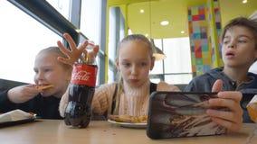Βαλτιμόρη, Μέρυλαντ, ΗΠΑ - 21 Φεβρουαρίου 2019: κορίτσι και αγόρι εφήβων που τρώνε το γρήγορο φαγητό και που πίνουν το κόκα κόλα  απόθεμα βίντεο